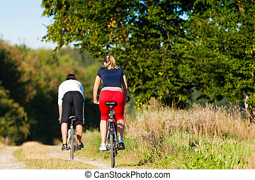 Man and woman exercising with bicycle