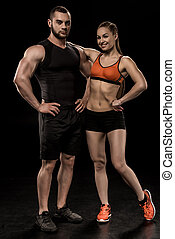 sportive man and woman posing together and looking at camera isolated on black