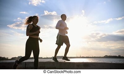 Sportive man and woman running by the waterfront. Mid shot