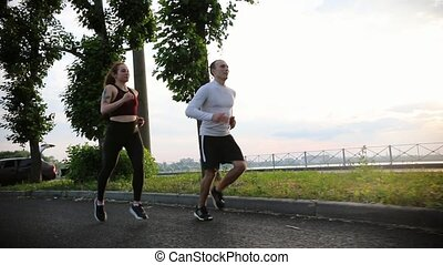 Sportive man and woman running on the path in the park at the early evening