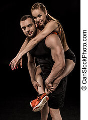 Sportive man looking at camera and piggybacking smiling woman isolated on black