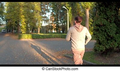 Sportive man runs in green autumn forest lightened with the sun