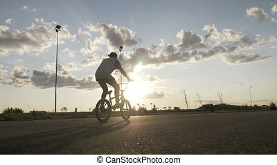 Sportive teenager relaxing on bike riding and doing tricks...
