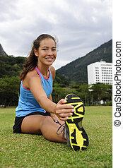 sportive, vrouw stretching, in het park