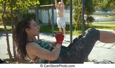 Sportive woman doing fitness exercises in front of muscular man athlete pulled-up on the bar outdoors at sunny day, slow-motion