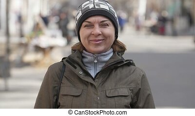 Sportive woman in knitted hat smiling and standing in a...