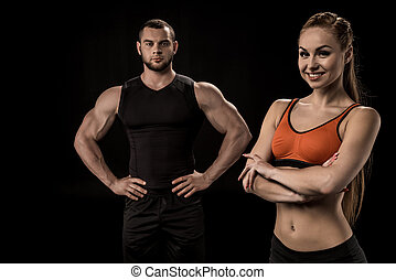 sportive woman looking at camera with man behind isolated on black
