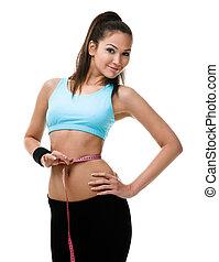 Sportive woman measures her waist