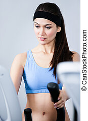 Sportive woman training on gym equipment in gym