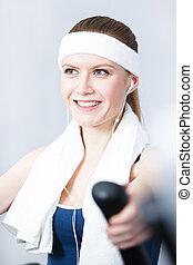 Sportive woman training on training apparatus in gym