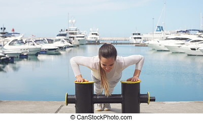 Sportive woman training outdoors doing crossfit exercise by the ocean pier.