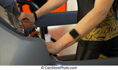 Sportive woman wearing smartwatch doing sport activity on treadmill