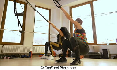 Sportive women doing push up exercise at the gym using...