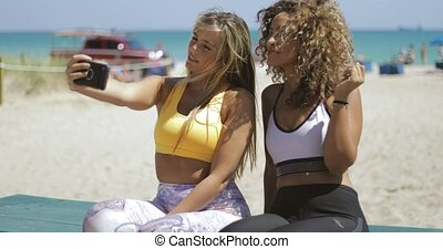 Sportive women taking selfie on beach - Confident diverse...