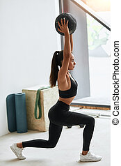 Sportive young brunette woman do lunges or squats with ball in gym