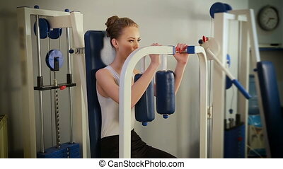 Sportive young woman doing exercise with simulator in the home gym