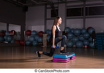 Sportive young woman with beautiful athletic body doing exercises with dumbbells. Fitness, bodybuilding. Healthcare