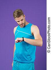 sportler, betrachten, fitness, uhr, auf, violett, hintergrund., mann, mit, sport, smartwatch, in, blaues, sportswear., spur, aktivität, und, workout., neue technologie, für, gesunde, lifestyle., sport, oder, fitness, und, wohlfühlen