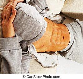 sportliche , mann, in, grau, hoodie, mit, muskulös, oberkörper, entspannend, auf, sofa
