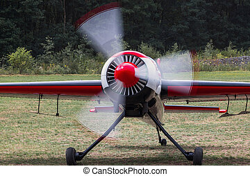 sports airplane with running motor on an airfield