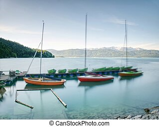 Sports boats, blue green mountain lake, windless day. -...