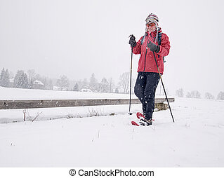 Sports body woman walk quickly with red hobby snowshoes