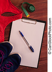 Sports bra, measuring tape and clipboard with pen