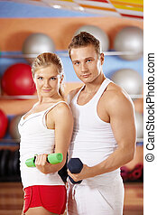 Sports club - Two beautiful trainers with dumbbells in hands...