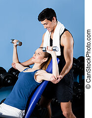 Sports coach helps woman to exercise with weights