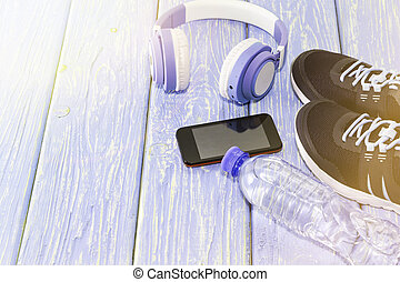Sports equipment. Sneakers water and headphones, on a light background