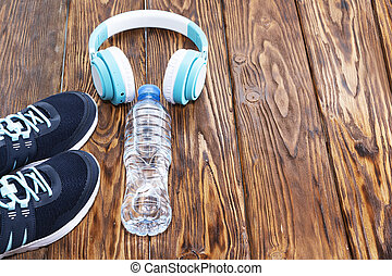 Sports equipment. Sneakers, water and headphones on wooden background