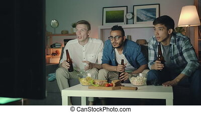 Sports fans watching game on TV clinking bottles laughing...