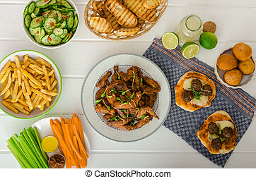 Sports feast - chicken wings, vegetable, french fries, pizza...