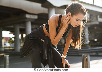 Sports fitness woman outdoors listening music