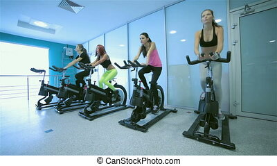 Sports friends pedaling and looks in front of a stationary bicycles at the gym