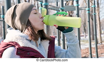Sports girl at an outdoor workout in a park on the sports field in the winter on a sunny day drinking water from a shaker.