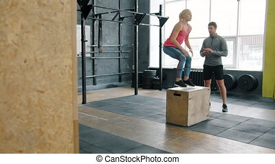 Sports girl busy with crossfit training jumping on wooden ...