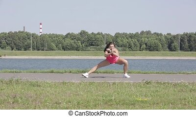 Sports girl does the workout outdoors
