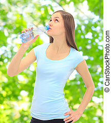 Sports girl drinking water on the