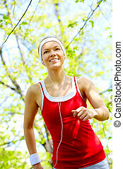 Sports girl - Portrait of a happy young woman jogging ...