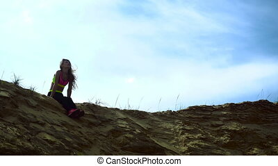 Sports girl resting on the Sandy Hill