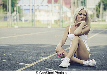 Sports girl sitting outdoors at the day time.