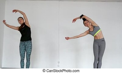 Sports girls in the Pilates lesson hold the arms above the head and move the body in a slant clockwise. Gymnastics