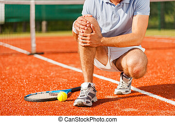 Sports injury. Close-up of tennis player touching his knee...