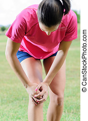 Sports Injury - Female athlete suffer from pain in her knee.