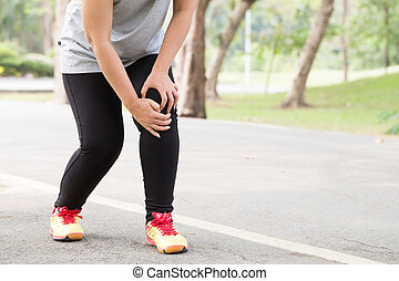 Sports injury. Woman with pain in knee while jogging