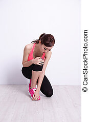 Sports injury. Young Woman fitness with pain in knee joint...