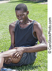 Sports leg injury - Young lean African American male athlete...