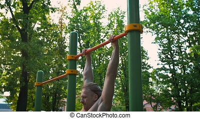 Sports lifestyle, street workout. Muscular man performs an exercise power outlet. Outdoor sports ground.