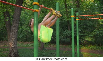 Sports lifestyle, street workout. Muscular man performing an exercise for the torso on the bar. Outdoor sports ground.
